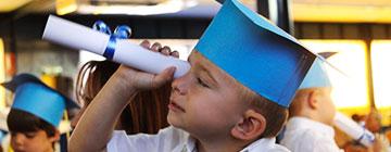 Imagen de un alumno con birrete mirando por un telescopio de papel